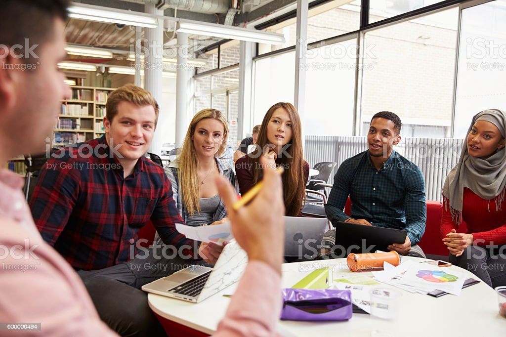 Group Of Students In Library Collaborating On Project stock photo