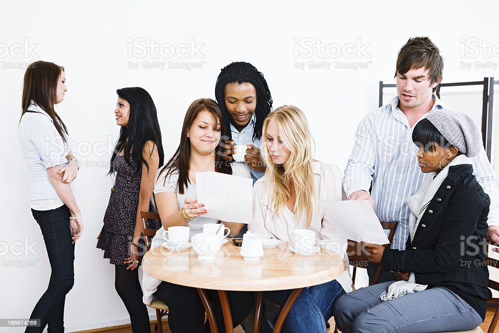 Group of students look at papers, possibly exams or results royalty-free stock photo