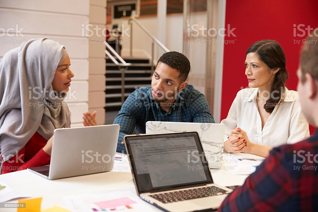 Group Of Students Meeting For Tutorial With Teacher stock photo