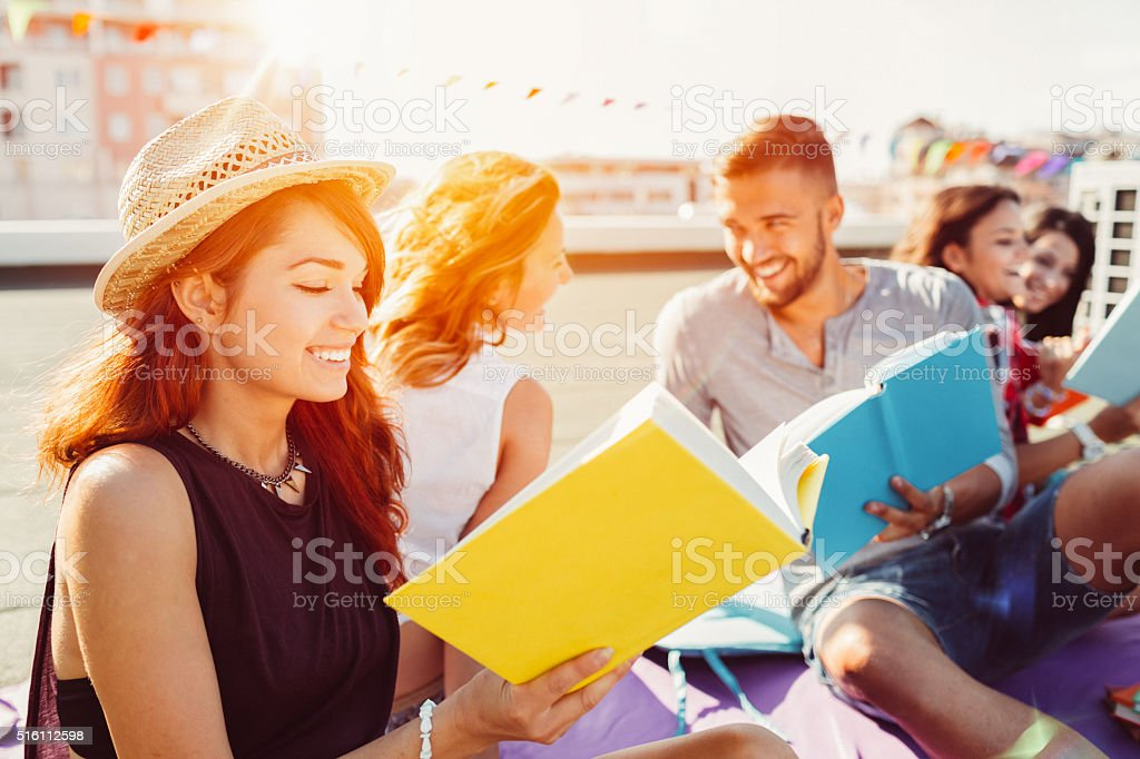 Group of students reading books on the rooftop stock photo