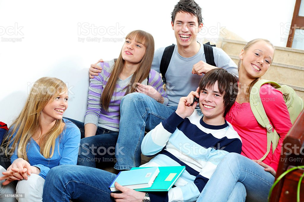 Group of students sitting on the stairs in a school. royalty-free stock photo