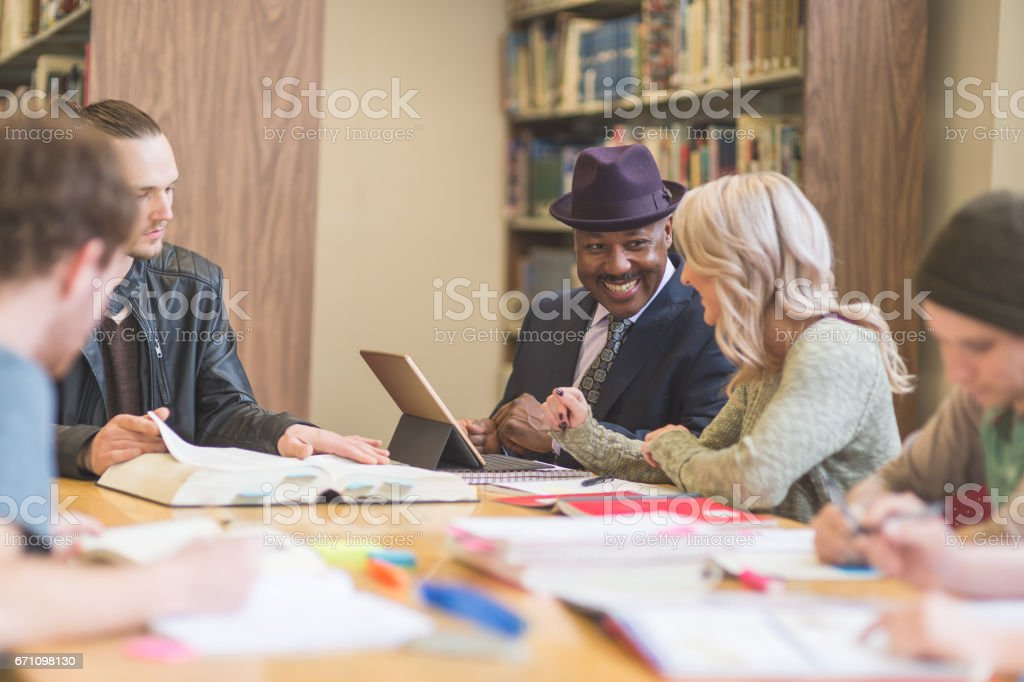Group of students study diligently in university library while a professor helps them understand the difficult concepts stock photo