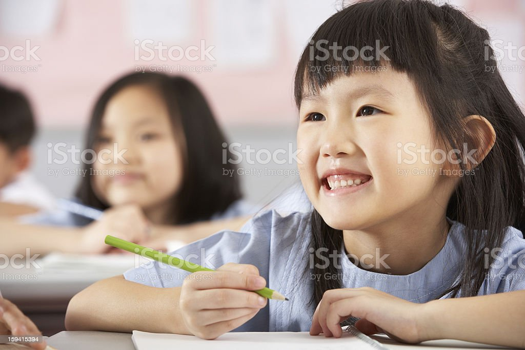 Group Of Students Working At Desks In Chinese School Classroom stock photo