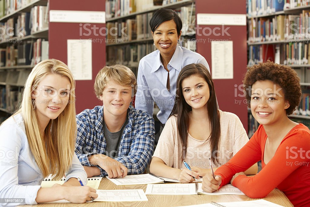 Group of students working in library with teacher royalty-free stock photo