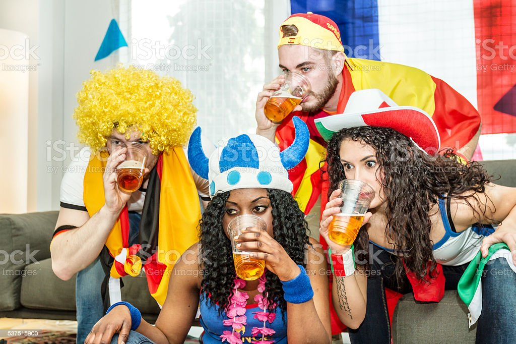 Group of supporters drinking beer at home stock photo