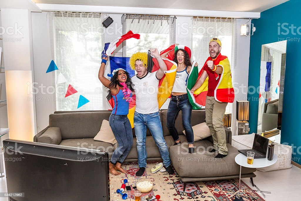 Group of supporters rejoices watching television stock photo