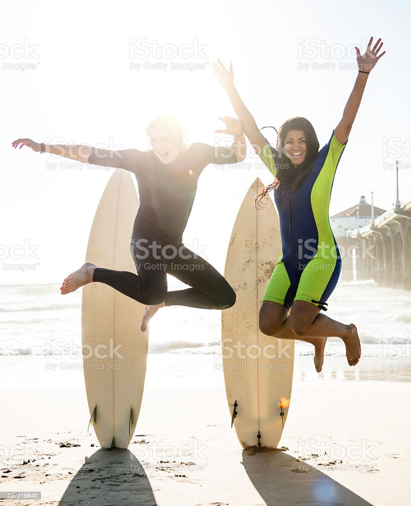 group of surfer friend jumping on the beach stock photo