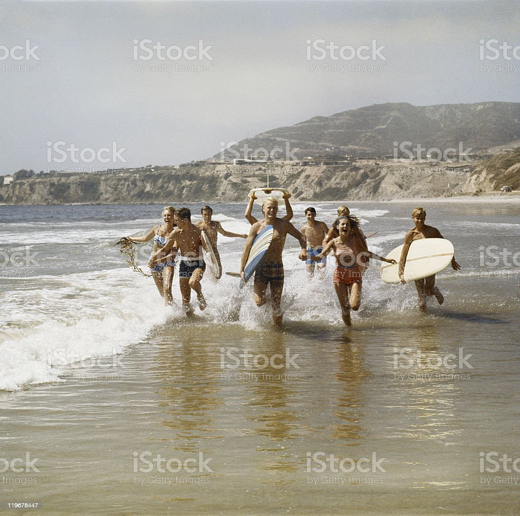 Group of surfers running in water with surfboards, smiling stock photo