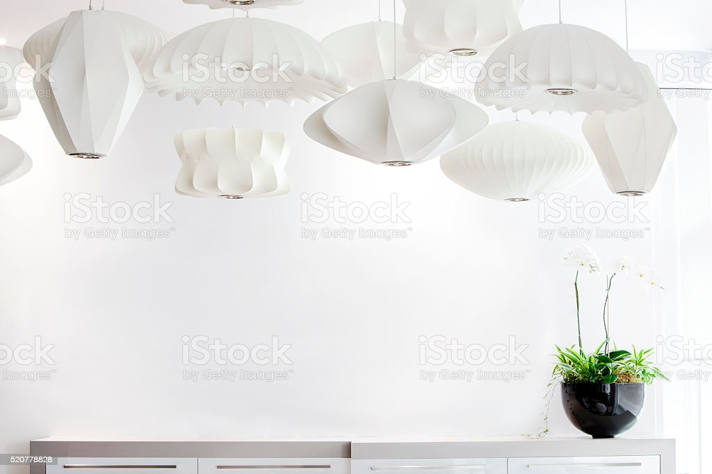 Group of suspended white lamp shades and orchid. stock photo