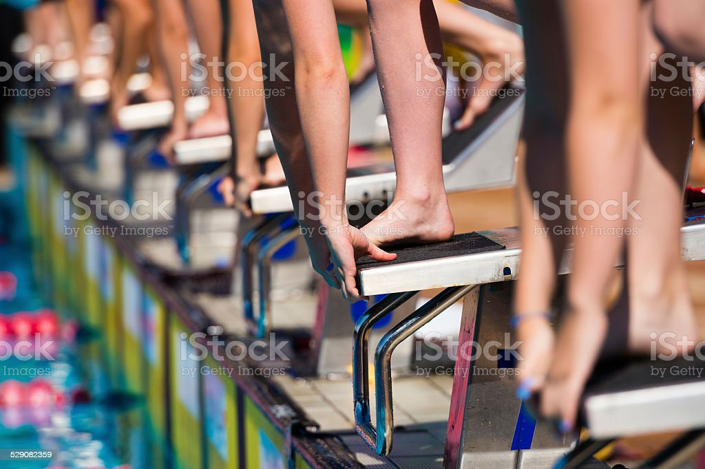 Group of Swimmers on the Blocks Waiting for Start stock photo