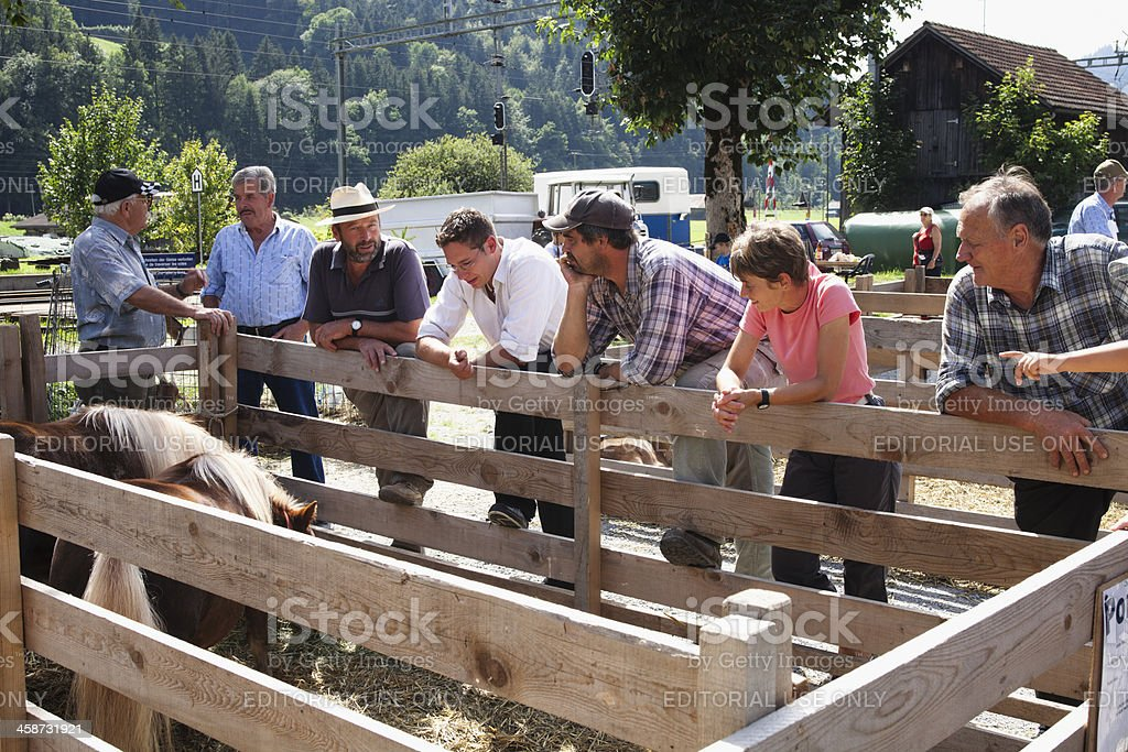 Group of Swiss Men Talking at Farmer's Market stock photo