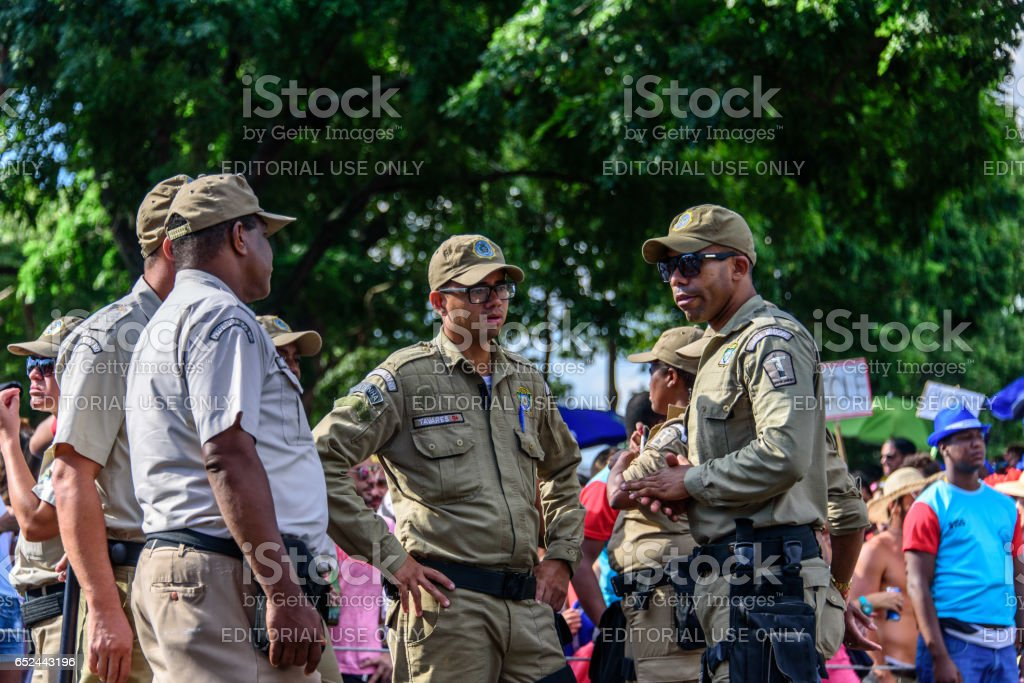 Group of talking policemen during Bloco Orquestra Voadora on the background of crowd of people, Carnaval 2017 stock photo