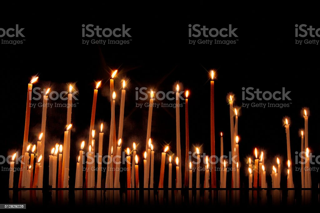 Group of tall candles on dark background stock photo