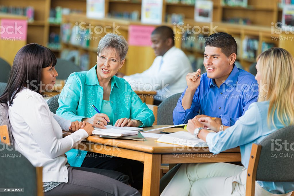 Group of teachers meet in library stock photo