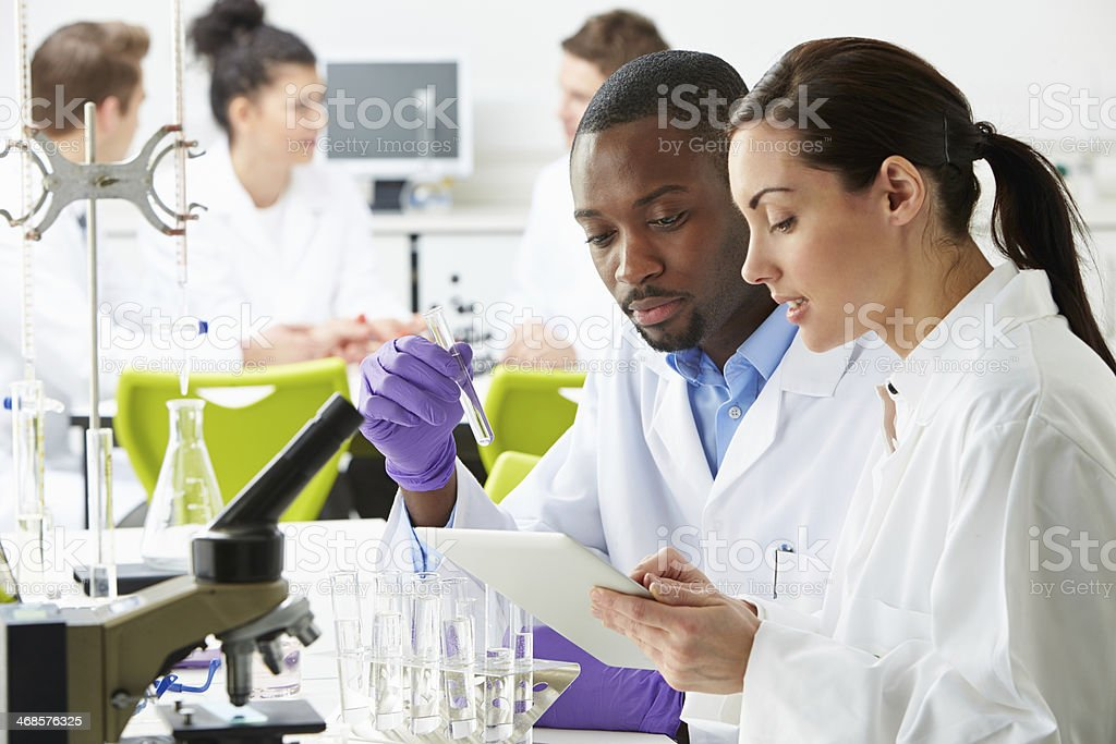Group Of Technicians Working In Laboratory stock photo