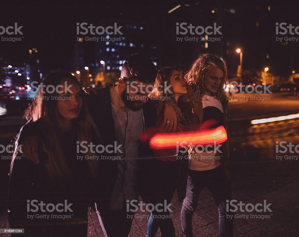 Group of teen hipster friend walking in town at night stock photo
