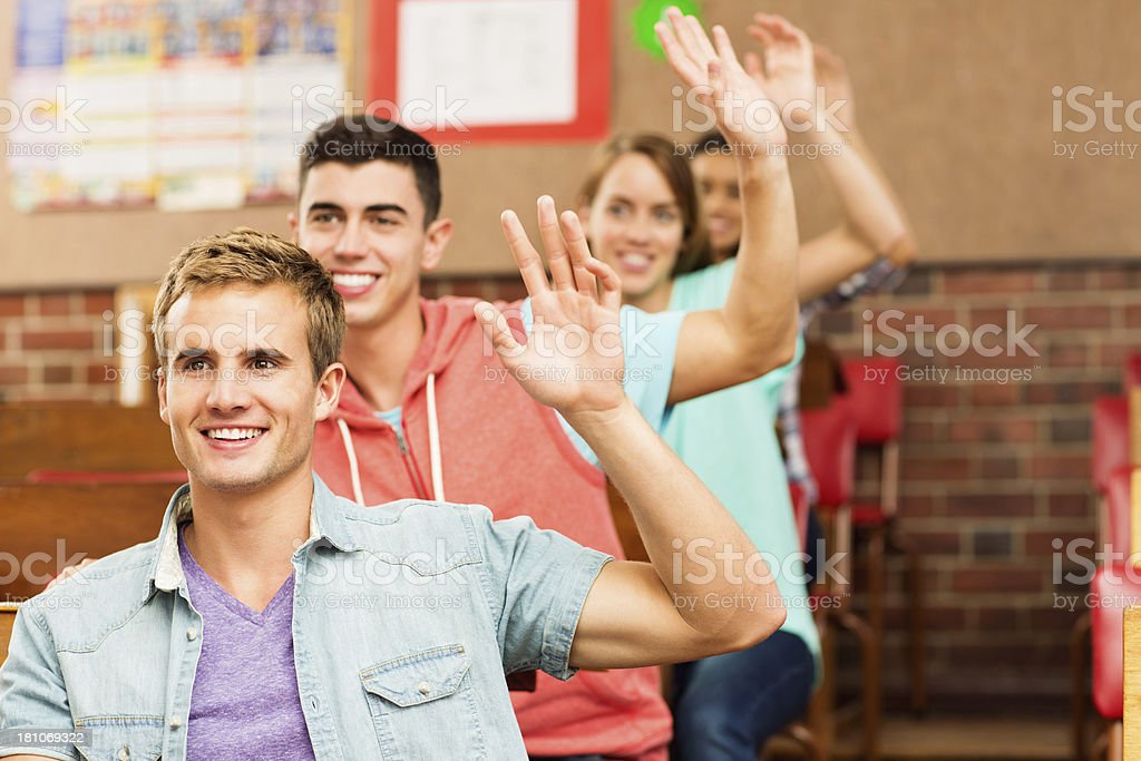 Group of Teen Students Raising Hands In Classroom royalty-free stock photo