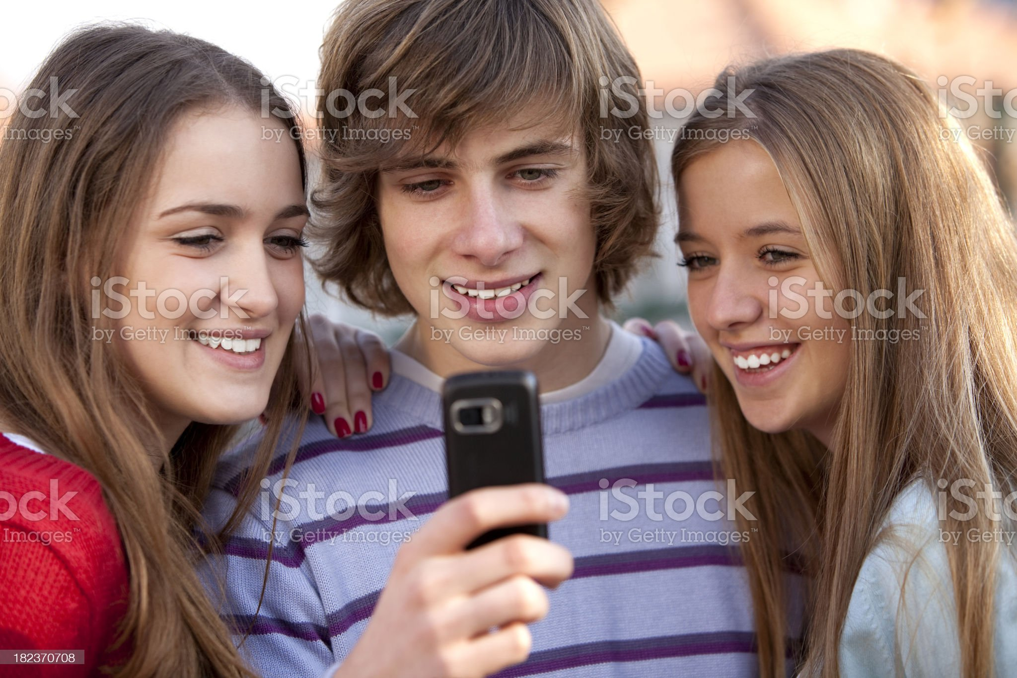 Group of teenage boys and girls looking on mobile phone royalty-free stock photo