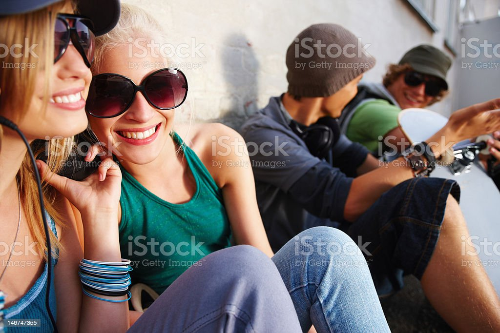 Group of teenage couples sitting together and having fun royalty-free stock photo