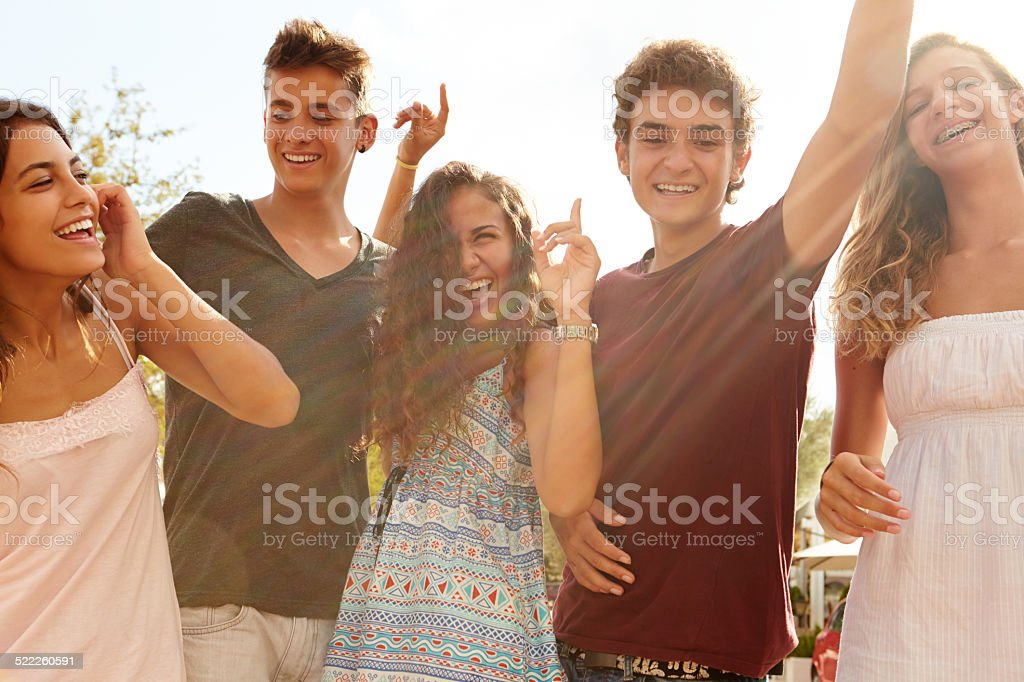 Group Of Teenage Friends Dancing Outdoors Against Sun stock photo
