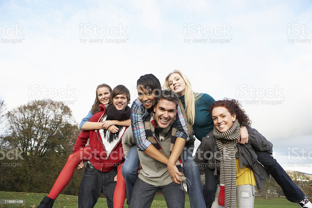 Group Of Teenage Friends Having Piggyback Rides In Autumn Landscape stock photo