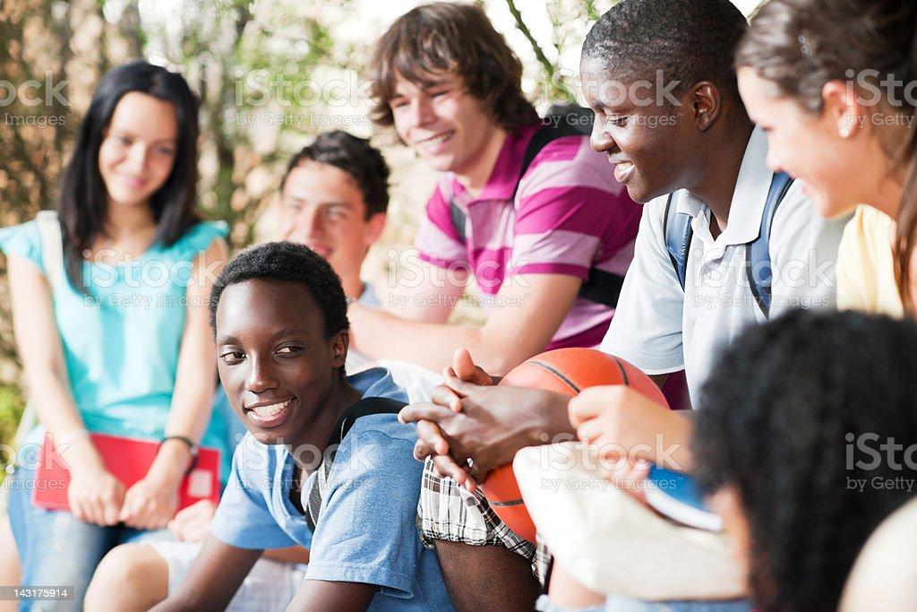 Group of teenage friends sitting on the bench. royalty-free stock photo