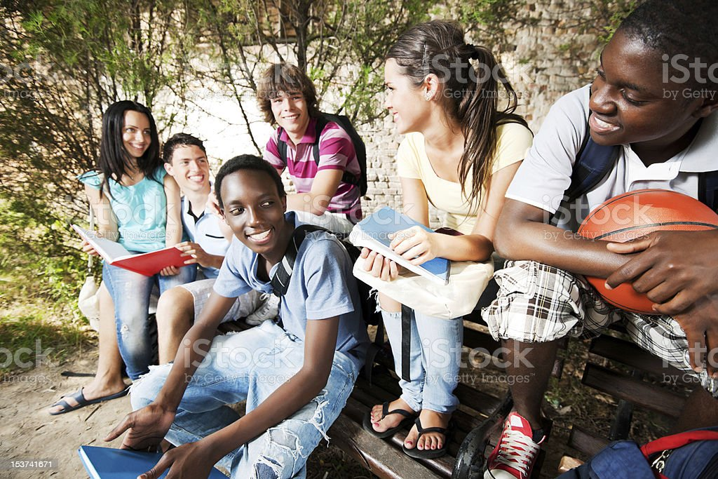 Group of teenage friends sitting on the bench. stock photo