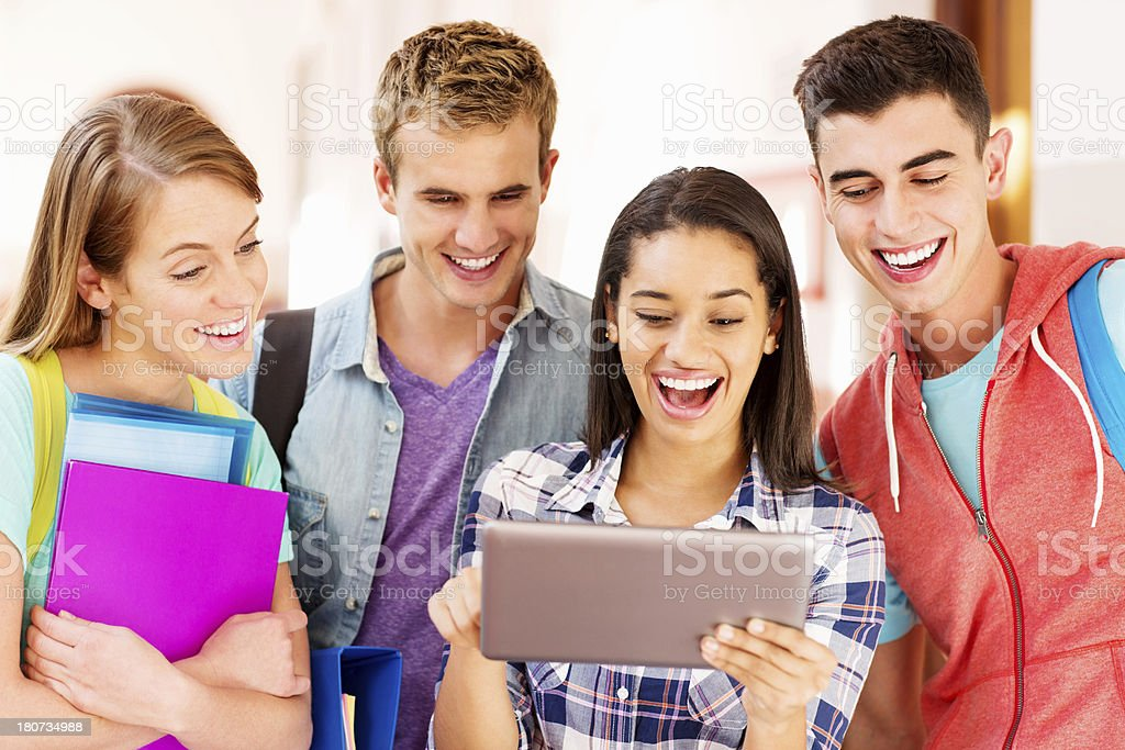 Group Of Teenage Friends Using Digital Tablet Together In College royalty-free stock photo