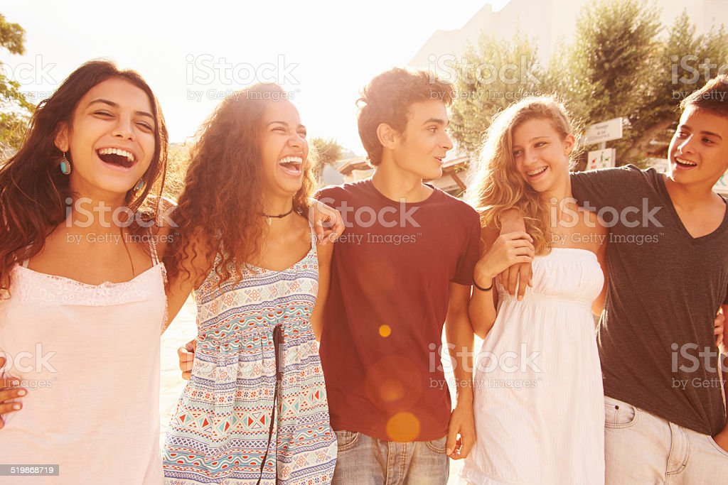 Group Of Teenage Friends Walking Along Street stock photo