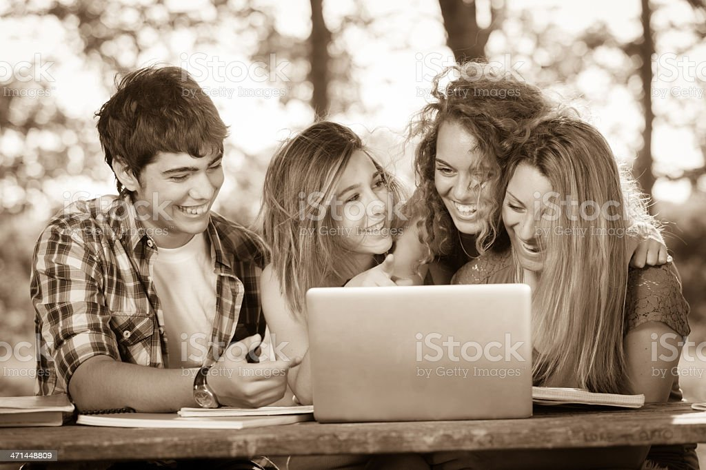 Group of Teenage Students at Park with Computer and Books stock photo