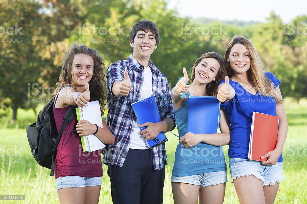 Group of Teenage Students at Park with Thumbs Up stock photo