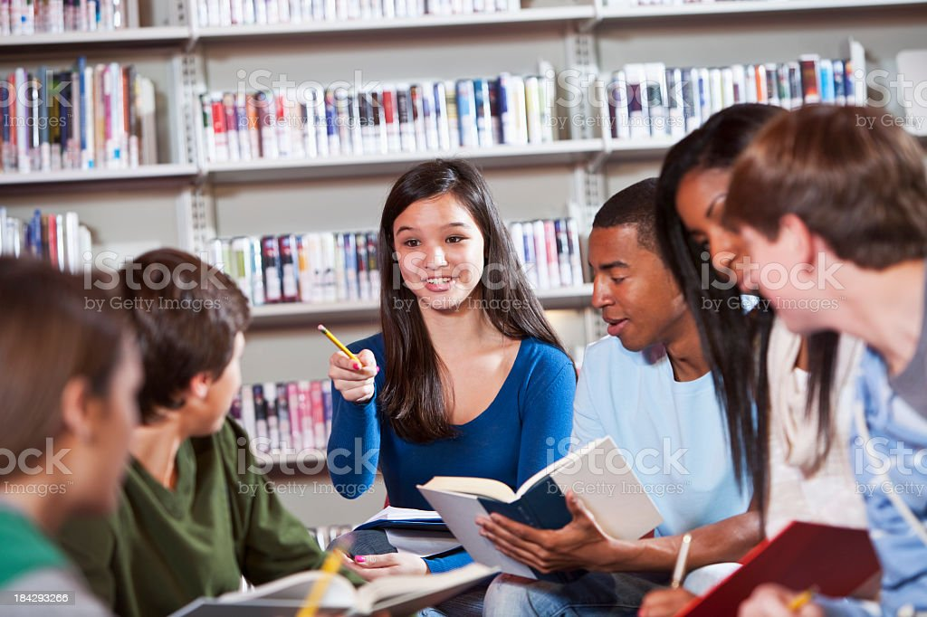 Group of teenage students discussing books stock photo