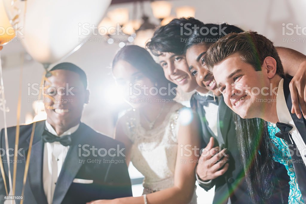 Group of teenagers at party wearing gowns and tuxedos stock photo