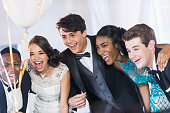 Group of teenagers at party wearing gowns and tuxedos