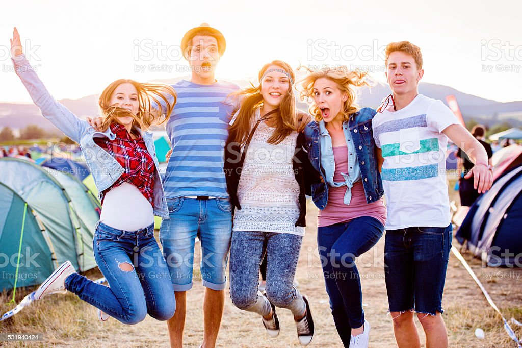 Group of teenagers at summer music festival, jumping stock photo