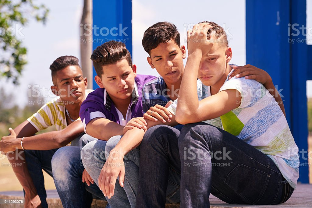 Group Of Teenagers Boys Supporting Comforting Friend stock photo