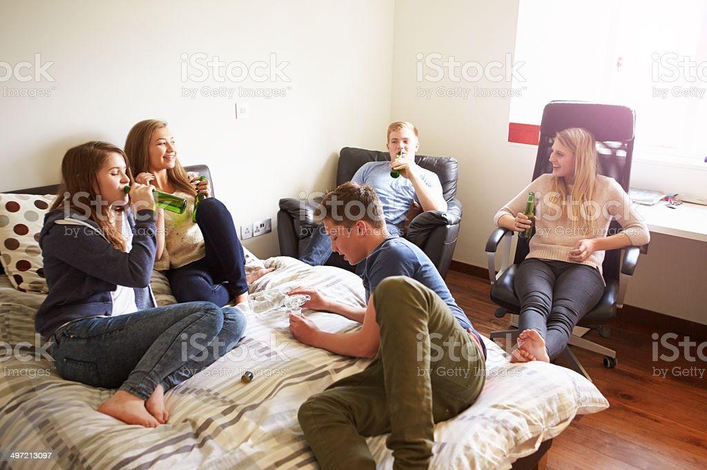 Group Of Teenagers Drinking Alcohol In Bedroom stock photo