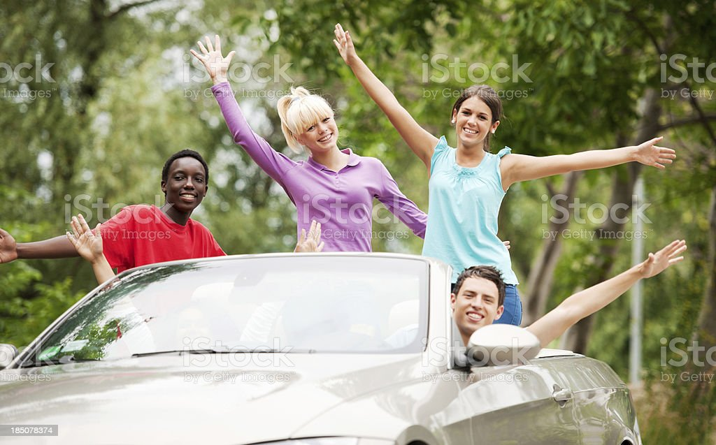 Group of smiling teenagers are enjoying while their friend is driving...