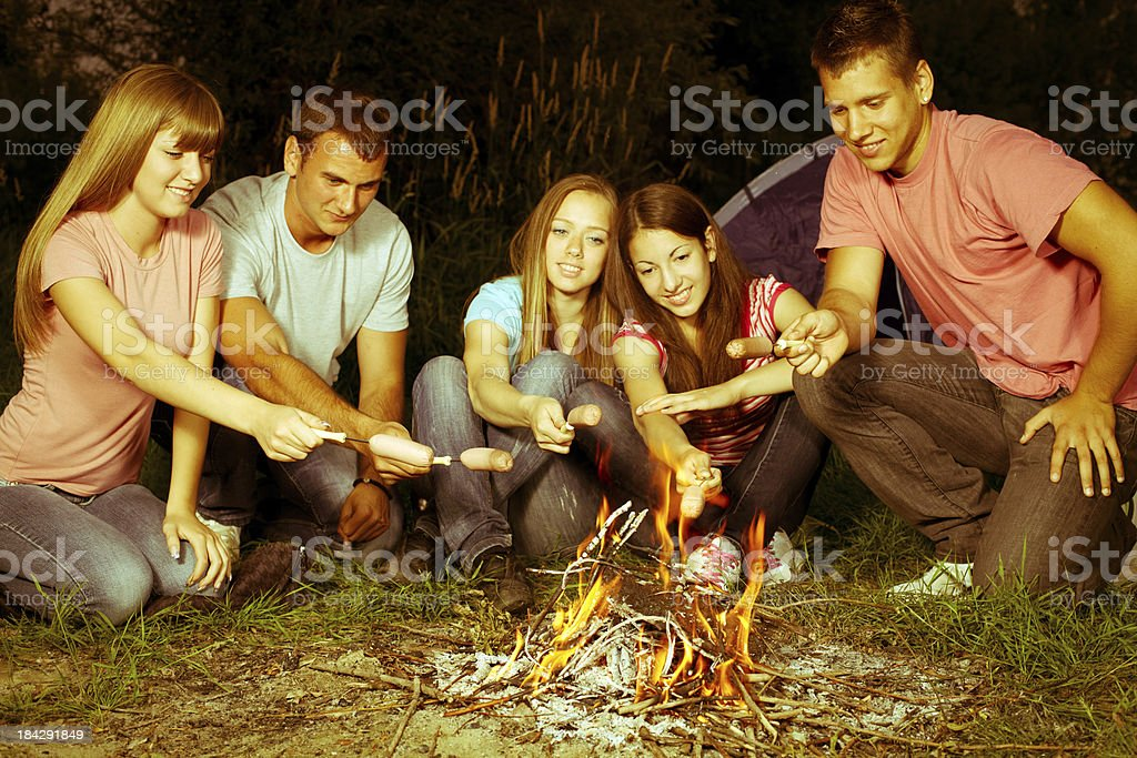 Group of teenagers grilling sausages on campfire. royalty-free stock photo