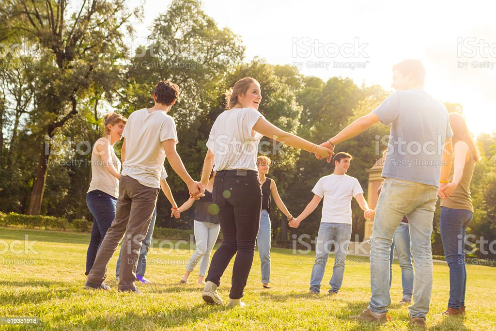 group of teenagers holding hands in a green field stock photo