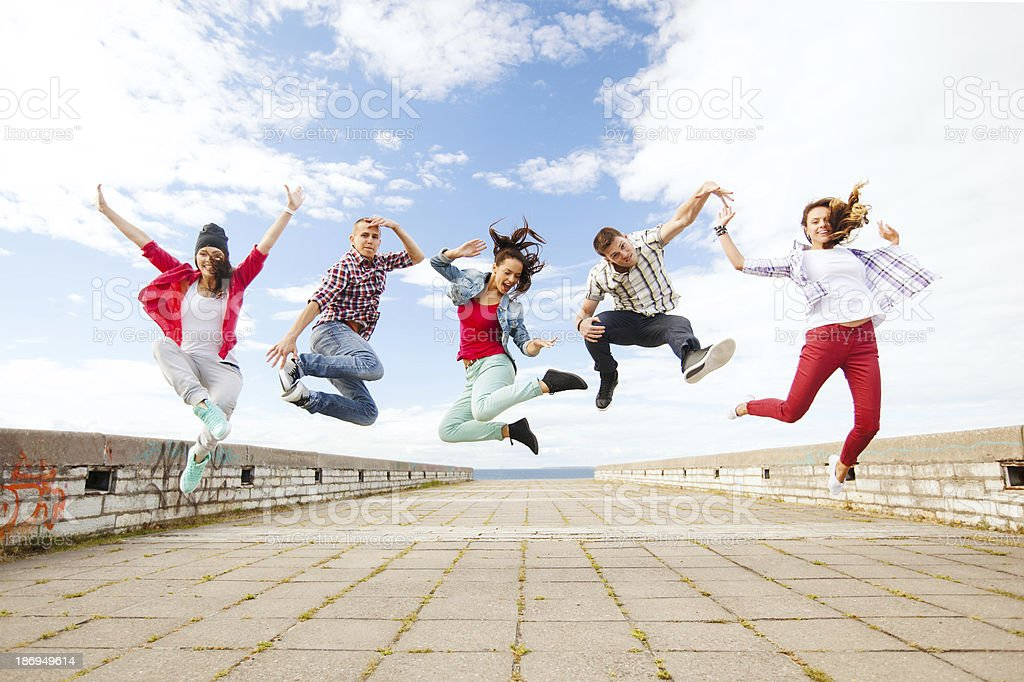 group of teenagers jumping on street stock photo
