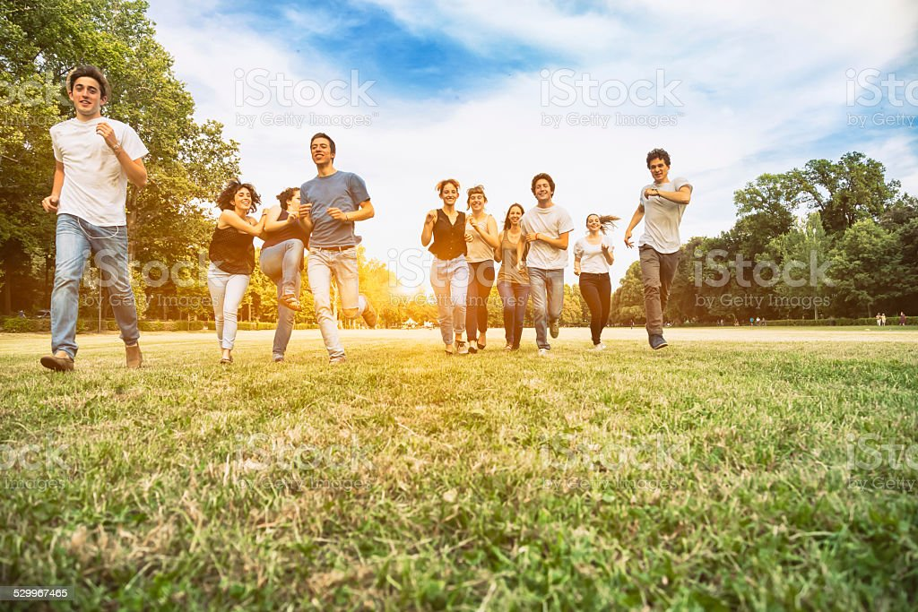Group of teenagers running in a park stock photo