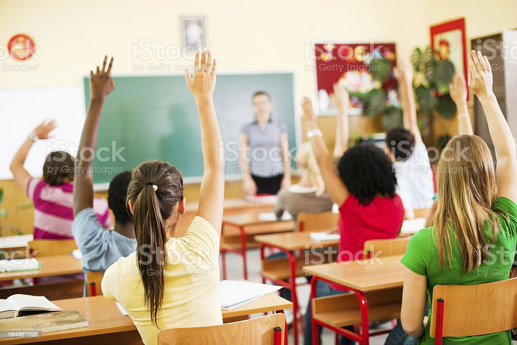 Group of teenagers sitting in classroom with raised hands. stock photo