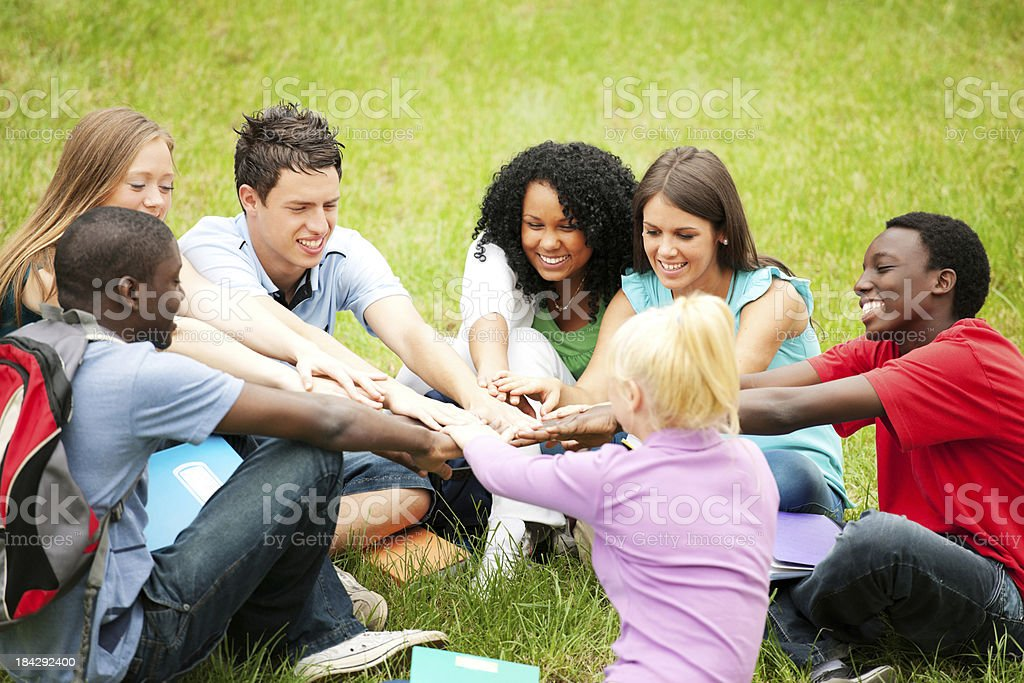 Group of teenagers sitting with hands pilled in centre. royalty-free stock photo