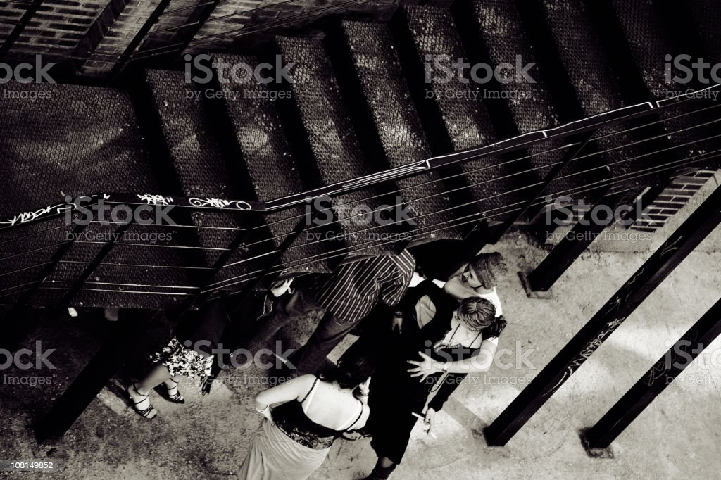 Group of Teenagers Under Grungy Staircase, Black and White stock photo