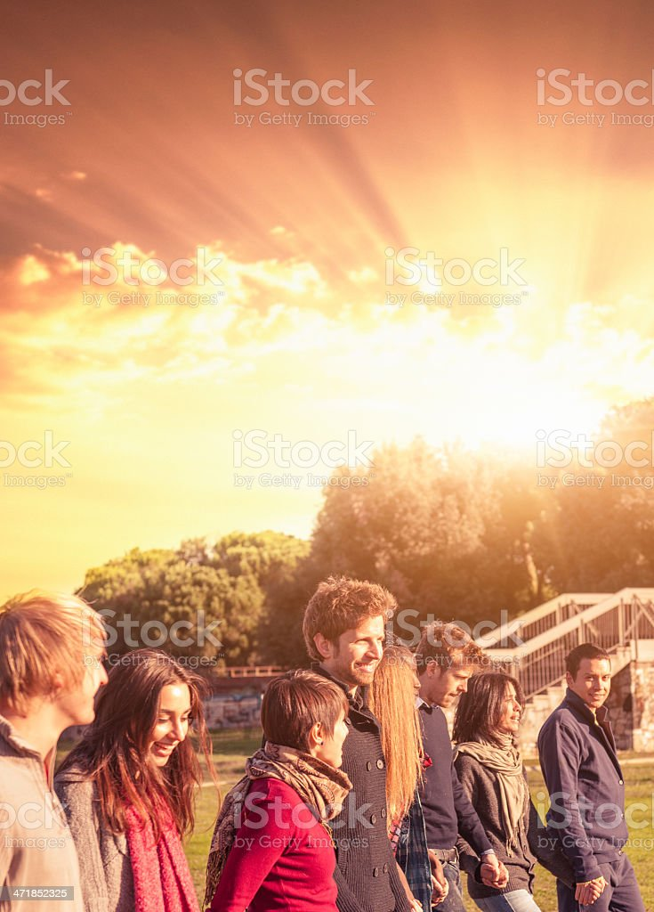 Group of teenagers walking in the park royalty-free stock photo