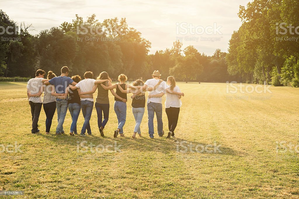 group of teenagers walking while holding together stock photo