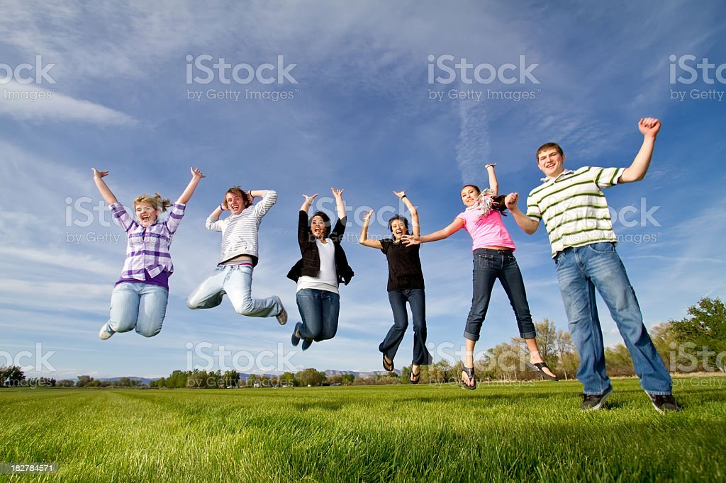 Group of teens jumping in a field royalty-free stock photo
