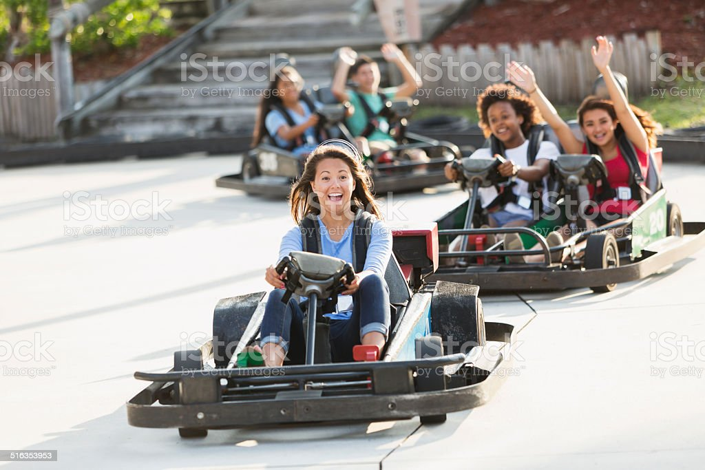 Group of teens riding go carts stock photo