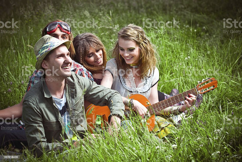 Group of teens sitting on the grass and playing guitar royalty-free stock photo